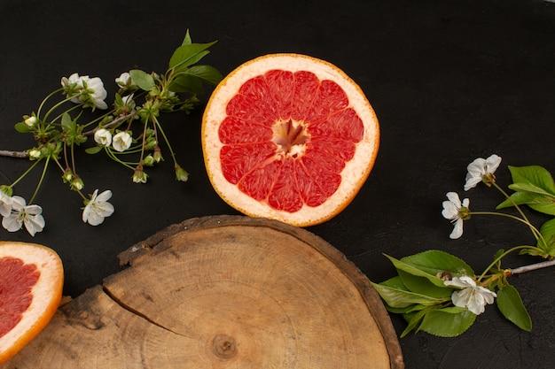 Вид сверху нарезанный грейпфрут вместе с белым цветком на темном полу