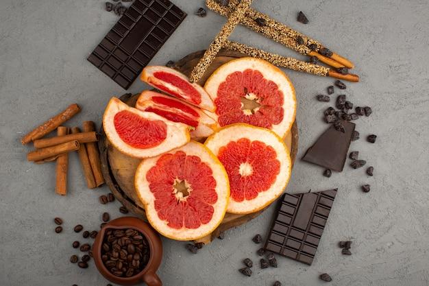 Вид сверху нарезанный грейпфруты сочно вместе с шоколадными батончиками и корицей на сером фоне