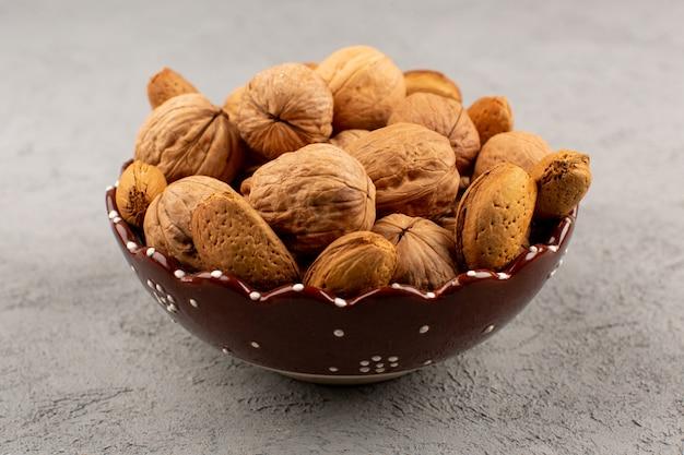Вид сверху грецкие орехи вся внутренняя тарелка на сером полу