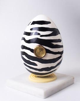 Вид спереди шоколадное яйцо в зебру раскраски черно-белое на подставке