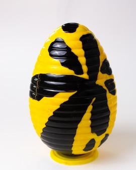 正面にチョコレートの卵が黄色、スタンドに黒