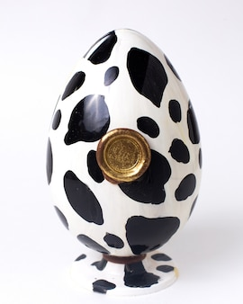 スタンドにゴールドシールが付いた正面の白と黒のチョコレートの卵の色