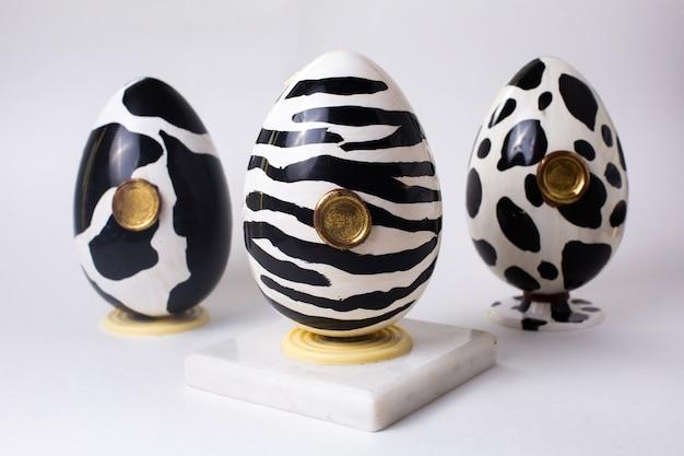 Вид спереди три шоколадных яйца черного и белого цвета в расцветке коровы зебры и долматинов на подставке