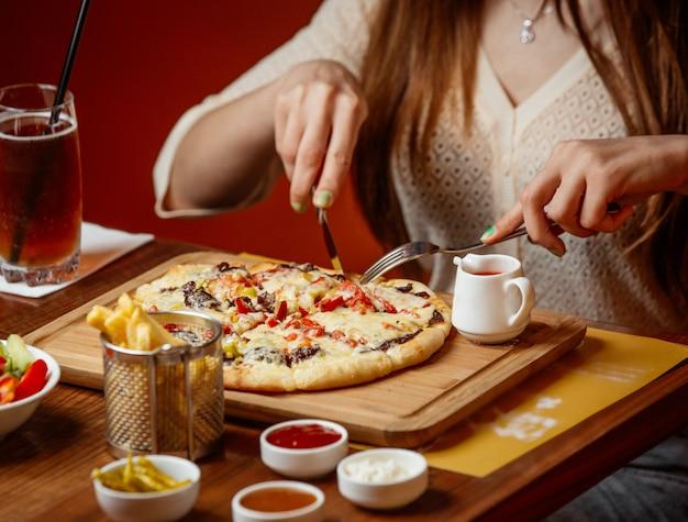 木の板に野菜とチーズの肉ピザ