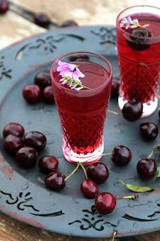 Вид сбоку два стакана вишневого сока с вишней на подносе
