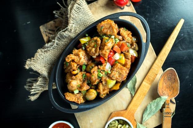ボード上のフライパンで野菜と揚げ肉のトップビュー