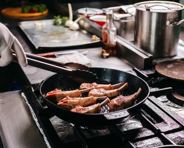 Готовим жареные мясные ребрышки внутри круглой металлической сковороды на кухне