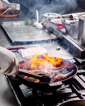 キッチンの黒い金属鍋の中に塩漬けのフライドリブ肉を調理する