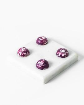 Разработанные шоколадные конфеты фиолетового цвета сладкие вкуснятина на белой поверхности