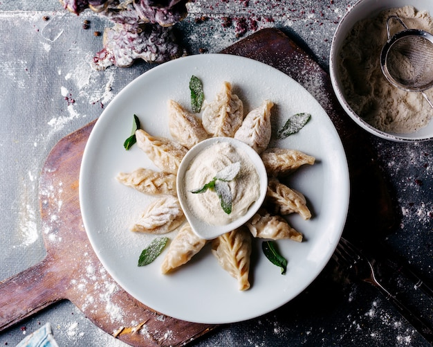 Блюдо из теста с начинкой из мяса с зелеными листьями и сметаной на коричневой деревянной поверхности