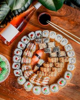 Рыбные рулетики вкусные вкусные свежие вместе с соусом на коричневой деревянной поверхности