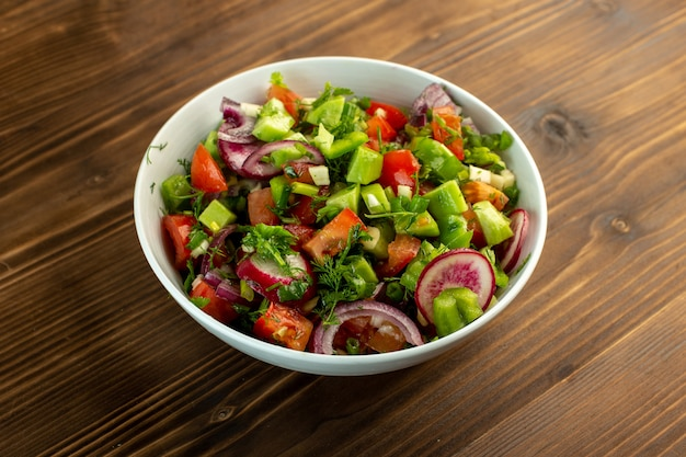 スライスしたキュウリの赤いトマトタマネギと木製の素朴な表面の白いプレート内の他のものを含む新鮮な野菜サラダ