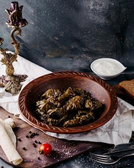 暗い表面の茶色のプレート内の緑のドルマ肉いっぱいの東部料理