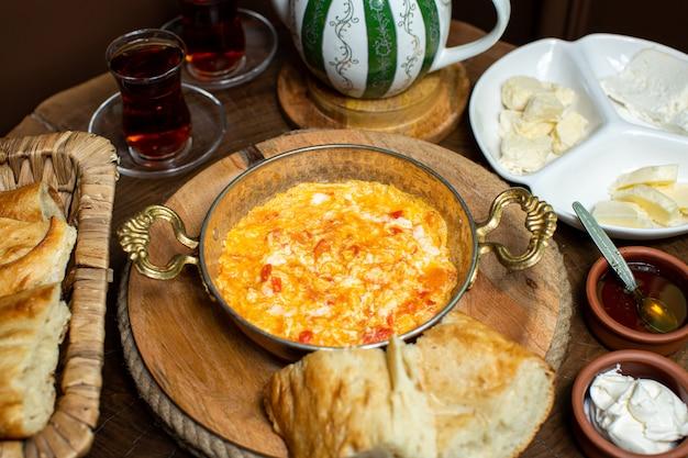 Вид спереди крупным планом приготовленные яйца с красными помидорами внутри металлической сковороде вместе с горячим чаем и кусочками хлеба