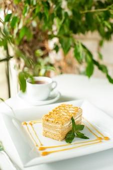 フロントクローズアップビュー白い表面に白いプレート内に設計された緑の葉でスライスされた黄色のケーキ