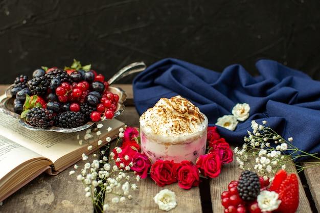 茶色の木製の素朴な机の上の赤いバラと新鮮な果実の周りのフロントクローズアップビューおいしいデザート