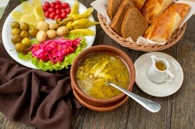 Горячий суп спереди, свежие овощи и ломтики хлеба