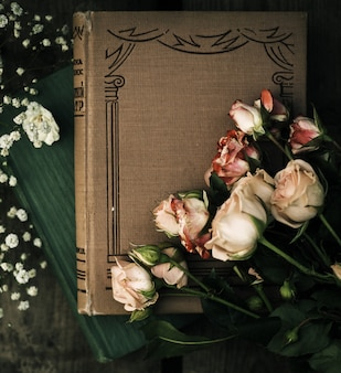 トップは灰色の机の上の本とバラを閉じます