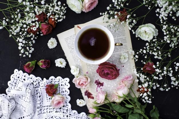 トップは、暗い表面に色とりどりのバラと一緒にビューの熱いお茶のカップを閉じます