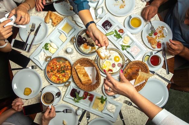 Семья завтрака таблицы взгляда сверху близкая вверх имея с различными едами