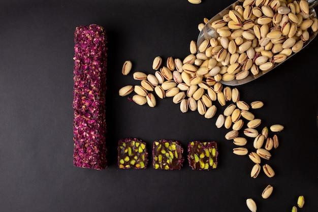 Вид сверху пурпурно-зеленой конфеты-батончика вкусного нарезанного вместе с арахисом на темном столе