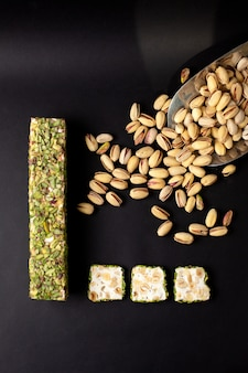 Вид сверху нарезанный батончик зеленого вкусного сладкого вместе с арахисом на темном столе
