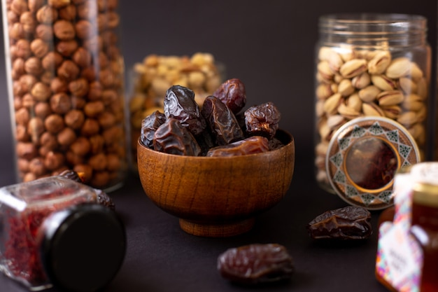 Вид спереди коричневого сладкого целого хурма вместе с орехами внутри стеклянных банок на темном полу