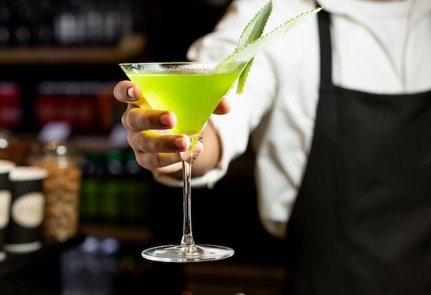 Желтый коктейль в руке бармена
