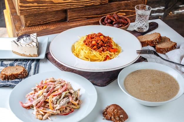 Вид спереди приготовленной пасты вместе со свежим салатом и супом на коричневой поверхности