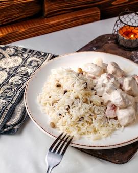 Вид спереди приготовленного риса вместе с бобами и кусочками мяса внутри белой тарелки на деревянной поверхности