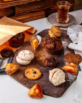 茶色の表面に正面の異なるクッキーとケーキ