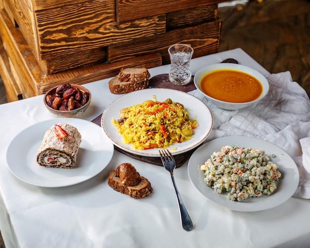 Вид спереди различных блюд, таких как приготовленные рисовые паштеты, мясные рулетики, салат и суп на белой поверхности
