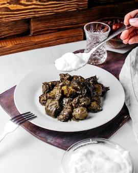Вид спереди долма вкусного восточного мясного блюда с белым йогуртом внутри белой тарелки на белом столе