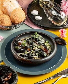 Чугунная кастрюля с мидиями в сливочном соусе, украшенная зеленью