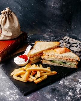 Вид спереди еды черный стол с картофелем фри и бутерброд на сером полу