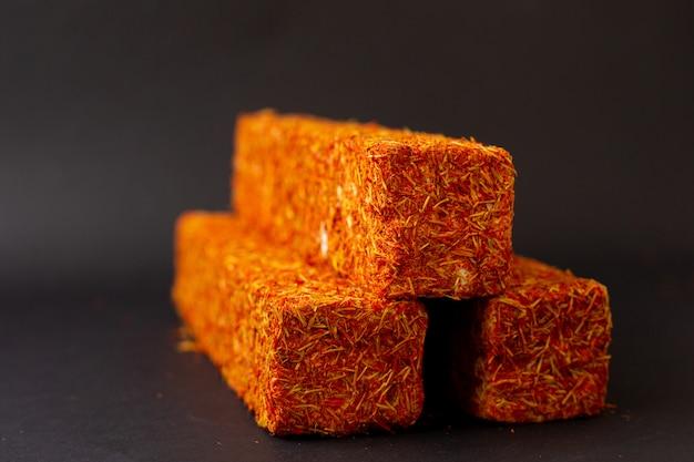 暗い机の上の正面オレンジキャンディバーおいしい甘い