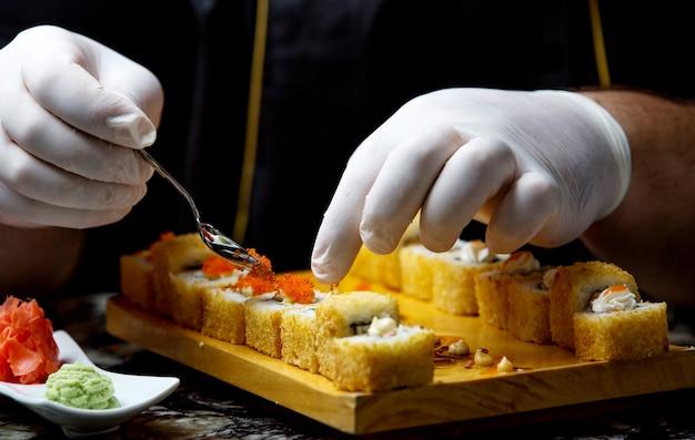 Суши из свежей рыбы с красной икрой на столе