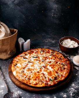 茶色の木製の丸い机と灰色の床に赤いトマトとチーズの正面ピザ