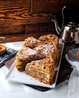 正面のおいしいケーキは茶色の床に白いプレート内のおいしいスライス