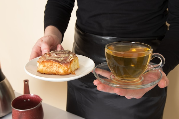 Бариста держит в руках торт и горячий зеленый чай