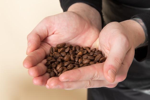 彼の手で保持している茶色のコーヒー種子バリストナ