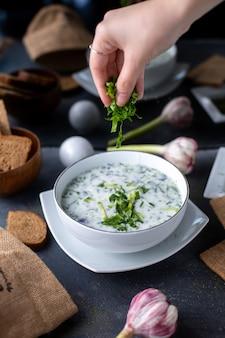 Зелень довга белый легкий суп с разными травами на сером