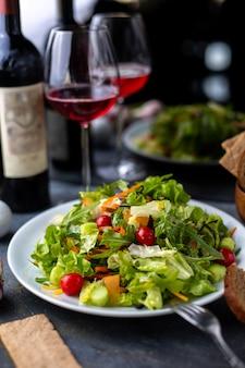 Нарезанная зелень овощи вместе с красным вином внутри белой тарелке
