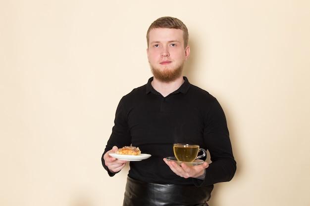 Молодой бариста держит торт и горячий зеленый чай