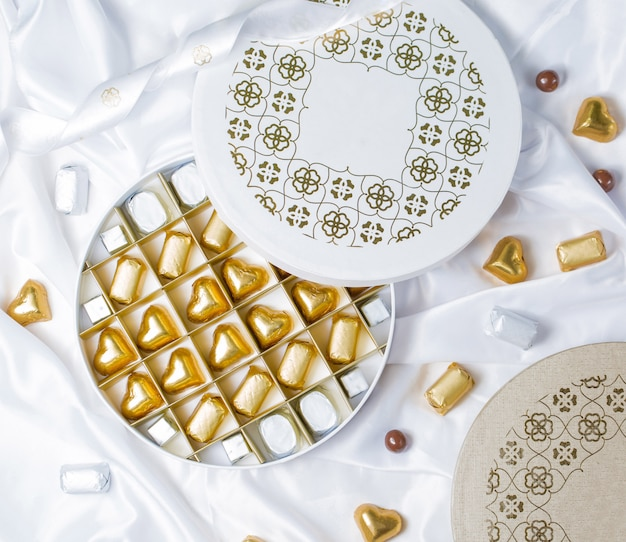 Вид сверху круглой шоколадной коробки с золотыми и серебряными конфетами