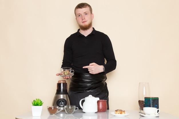 Молодой бариста в черном рабочем костюме с ингредиентами и кофейным оборудованием