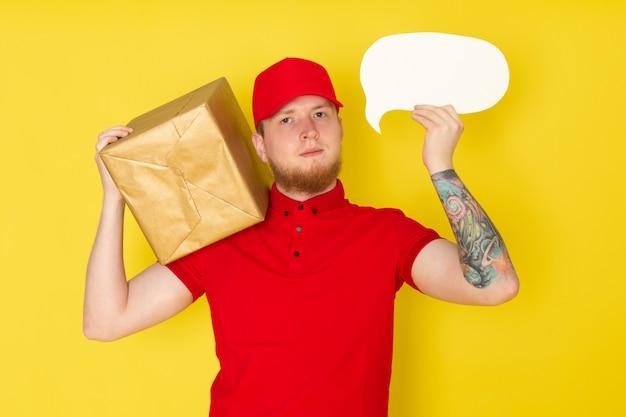 黄色のボックスを保持している赤いポロ赤い帽子白いジーンズの若い配達人