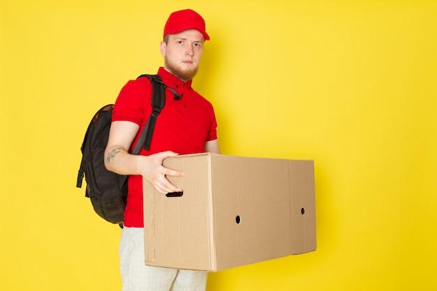 Молодой доставщик в красной поло красная шапочка белые джинсы держит коробку на желтом