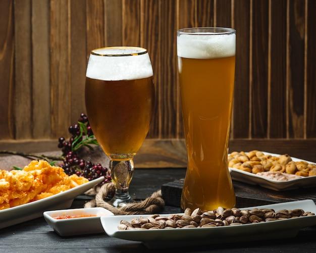 Два бокала пива подаются с фисташками, наггетсами и сладким соусом чили