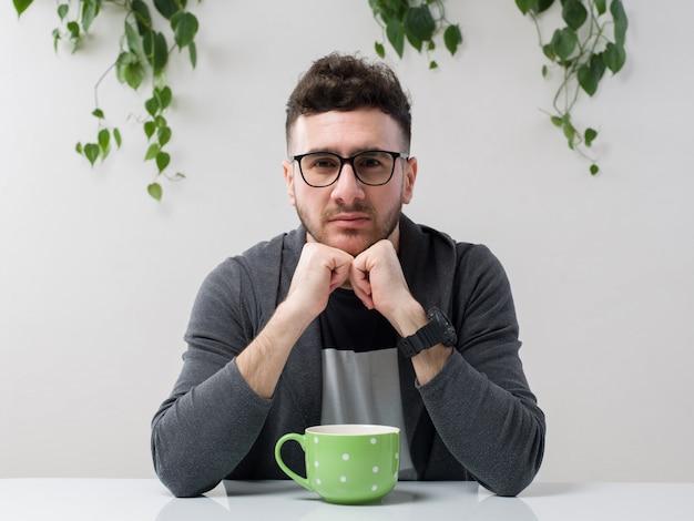 眼鏡に座っている若い男は白の植物と共に灰色のジャケットを見る